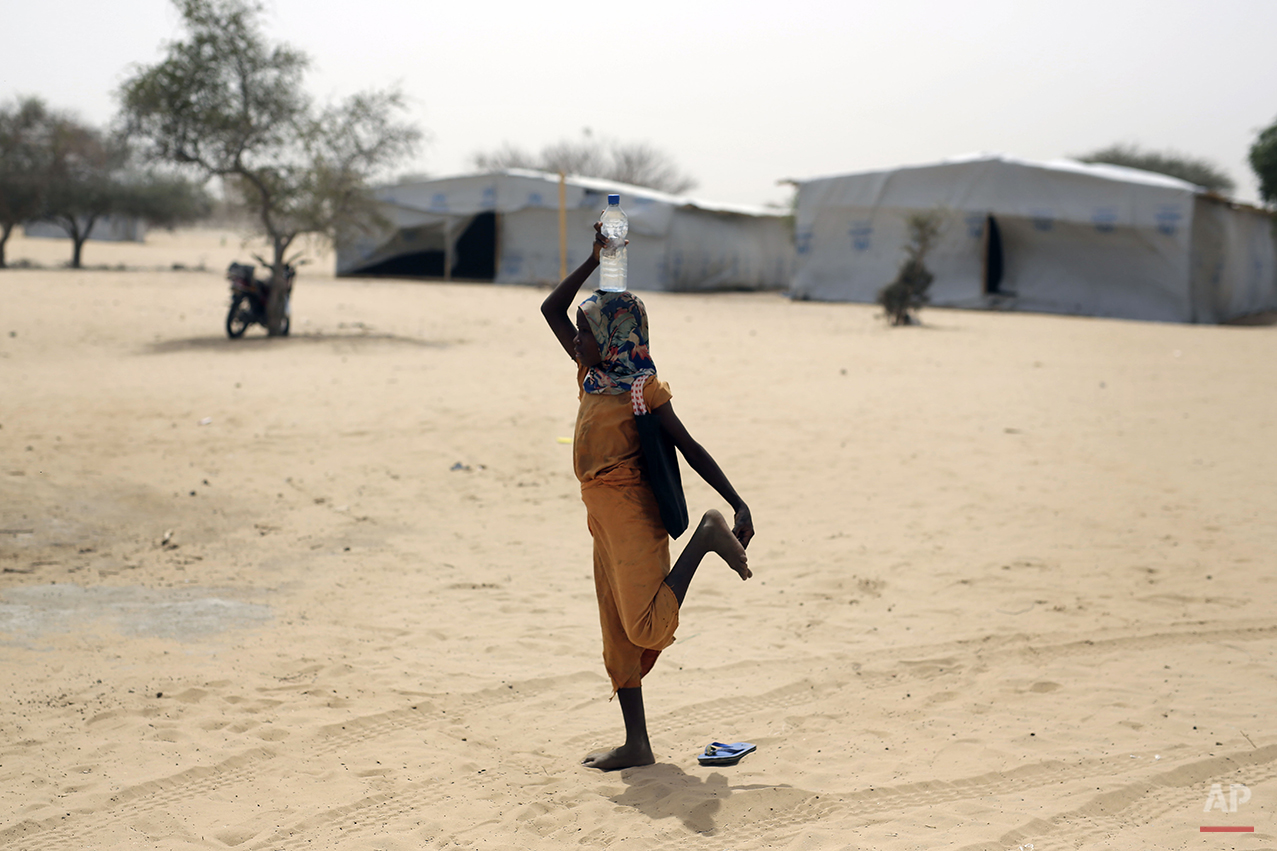 A Nigerian girl who fled Boko Haram to Chad removes a thorn from her foot at the Baga Solo refugee camp near the shore of Lake Chad, Wednesday March 4, 2015. The camp, jointly run by the Chadian government and UNHCR, opened mid-January 2015 and hosts over 6000 refugees. Officials say that several thousand had arrived in Chad by the end of 2014 as Boko Haram intensified its attacks in the area. (AP Photo/Jerome Delay)
