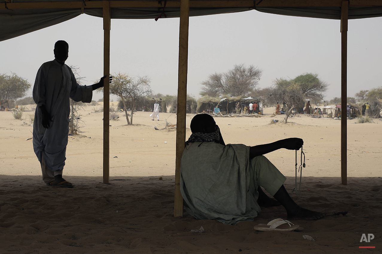 Nigerians who fled Boko Haram to Chad sit in a tent at the Baga Solo refugee camp near the shore of Lake Chad, Wednesday March 4, 2015. The camp, jointly run by the Chadian government and UNHCR, opened mid-January 2015 and hosts over 6000 refugees. Officials say that several thousand had arrived in Chad by the end of 2014 as Boko Haram intensified its attacks in the area. (AP Photo/Jerome Delay)