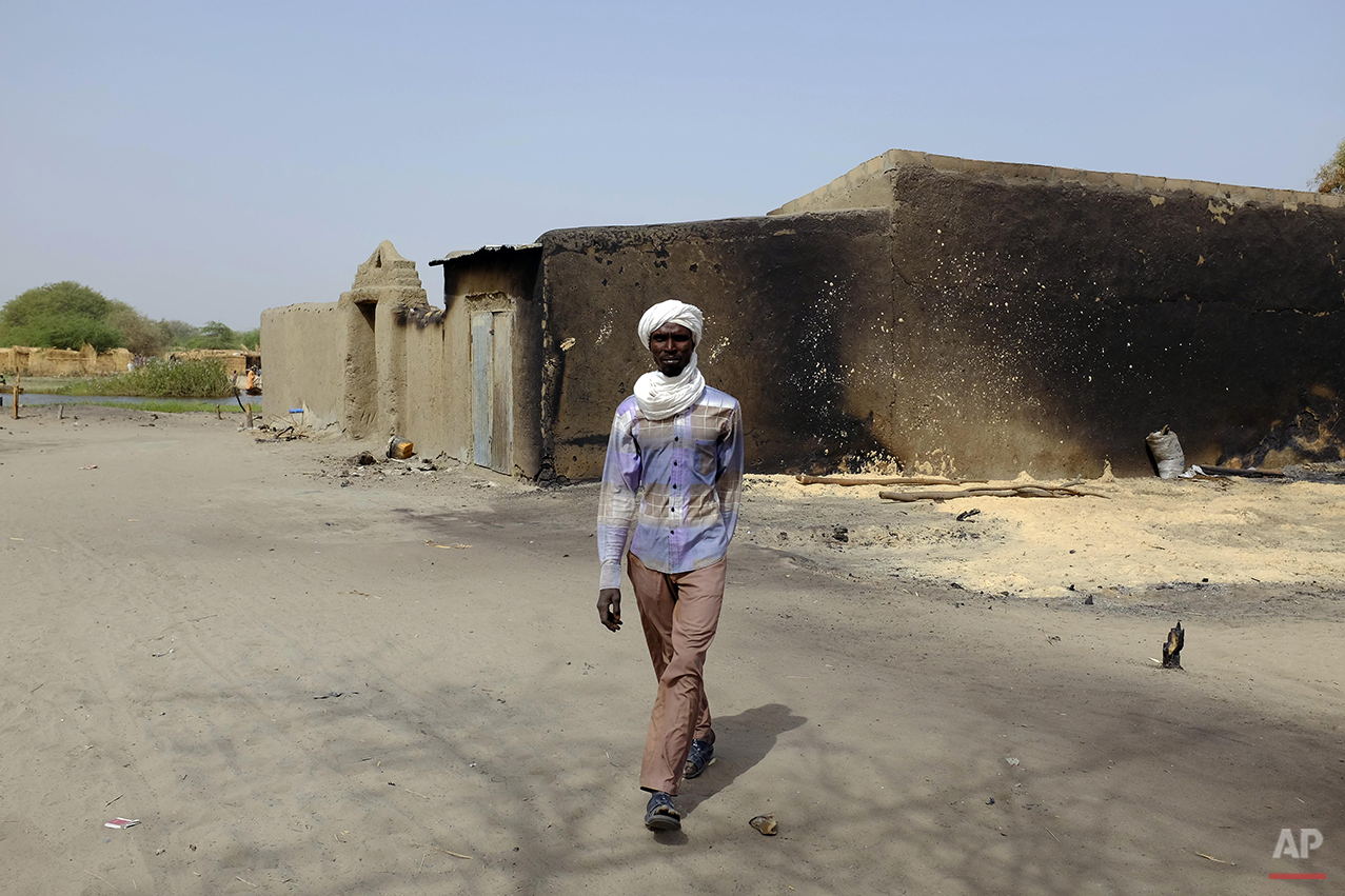 A man walks past a a house bearing burn marks in the Lake Chad shore village of  N'Gouboua Thursday March 5, 2015. Boko Haram militants arrived in N'gouboua before dawn on Feb. 13, marking the first attack of its kind on Chad. By the time the scorched-earth attack ended, they had burned scores of mud-brick houses by torching them with gasoline and had killed at least eight civilians and two security officers. Some 3,400 Nigerian refugees had been living in te village at the time of the attack, and all have since been relocated further inland. (AP Photo/Jerome Delay)