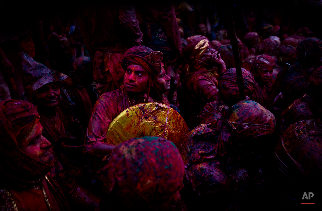 In this Saturday, Feb. 28, 2015 photo, Indian Hindu devotees smeared with colors visit the Nandagram temple, famous for Lord Krishna and his brother Balram, during Lathmar Holi festival, in Nandgaon, India. During Lathmar Holi the women of Nandgaon, the hometown of Krishna, beat the men from Barsana, the legendary hometown of Radha, consort of Hindu God Krishna, with wooden sticks in response to their teasing as they depart the town. (AP Photo/Saurabh Das)