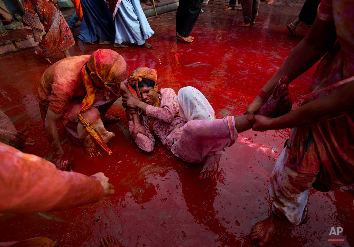 Indian Hindu men smeared with colors play holi during Lathmar festival celebrations in Nandgaon, India, Saturday, Feb. 28, 2015. During Lathmar Holi the women of Nandgaon, the hometown of Krishna, beat the men from Barsana, the legendary hometown of Radha, consort of Hindu God Krishna, with wooden sticks in response to their teasing as they depart the town. (AP Photo/Saurabh Das)