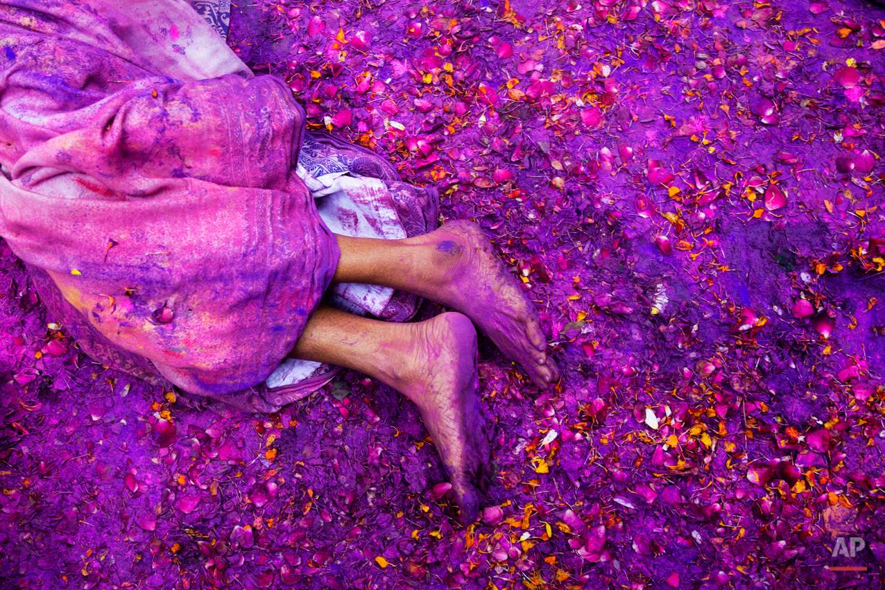 A Hindu widow lies on a sludgy ground filled with a mixture of colored powder, water and flower petals during celebrations to mark Holi, the Hindu festival of colors, at the Meera Sahabhagini Widow Ashram in Vrindavan, India, Tuesday, March 3, 2015. After their husband's deaths many of the women in the ashrams have been banished by their families, for supposedly bringing bad luck, while some move voluntarily to and around the town where devotees believe Lord Krishna was born. (AP Photo/Bernat Armangue)