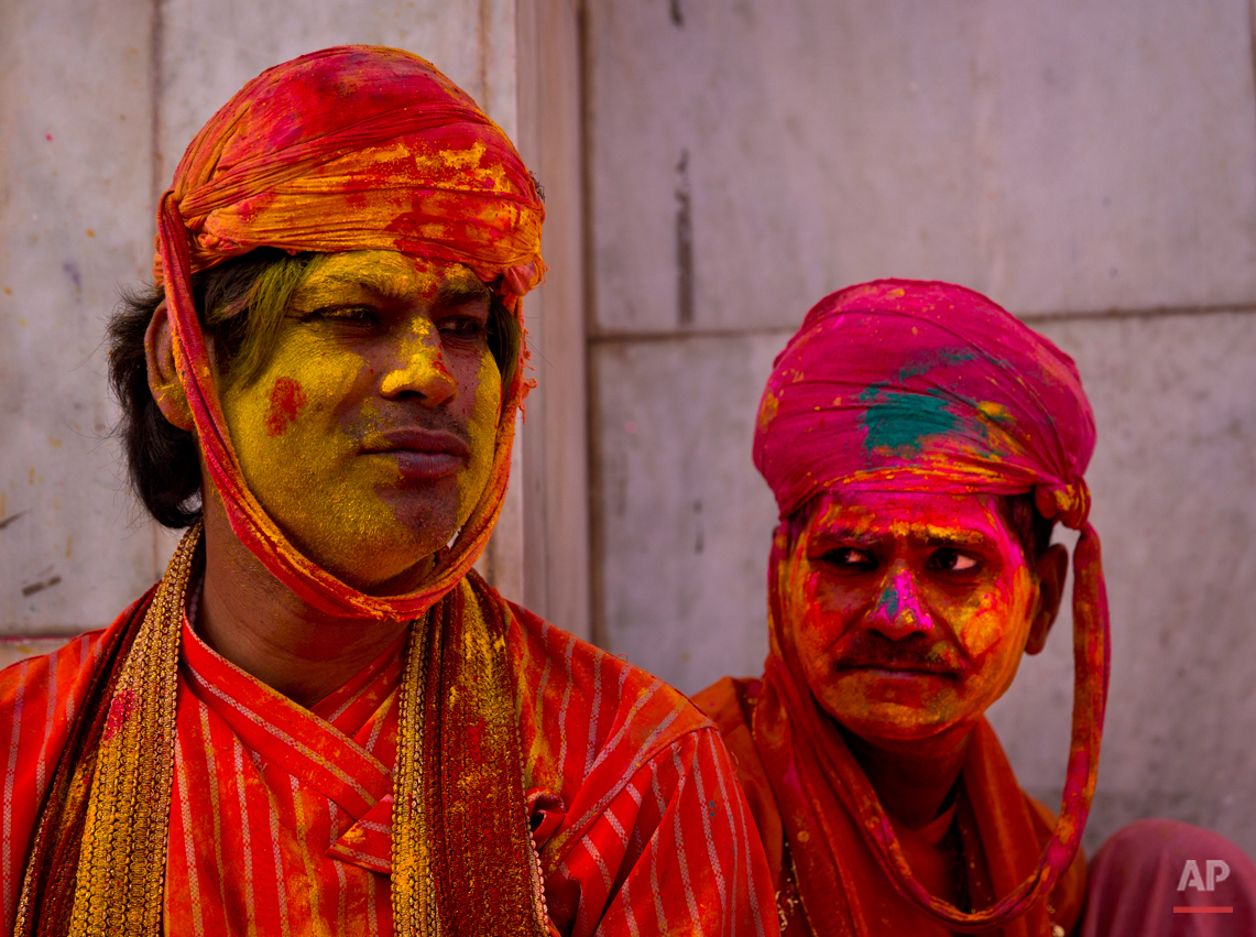 Indian villagers from Nandgaon wait for the arrival of villagers from Barsana at the Nandagram temple, famous for Lord Krishna and his brother Balram, during Lathmar holi festival, in Nandgaon, India, Saturday, Feb. 28, 2015. During Lathmar Holi the women of Nandgaon, the hometown of Krishna, beat the men from Barsana, the legendary hometown of Radha, consort of Hindu God Krishna, with wooden sticks in response to their teasing as they depart the town. (AP Photo/Saurabh Das)