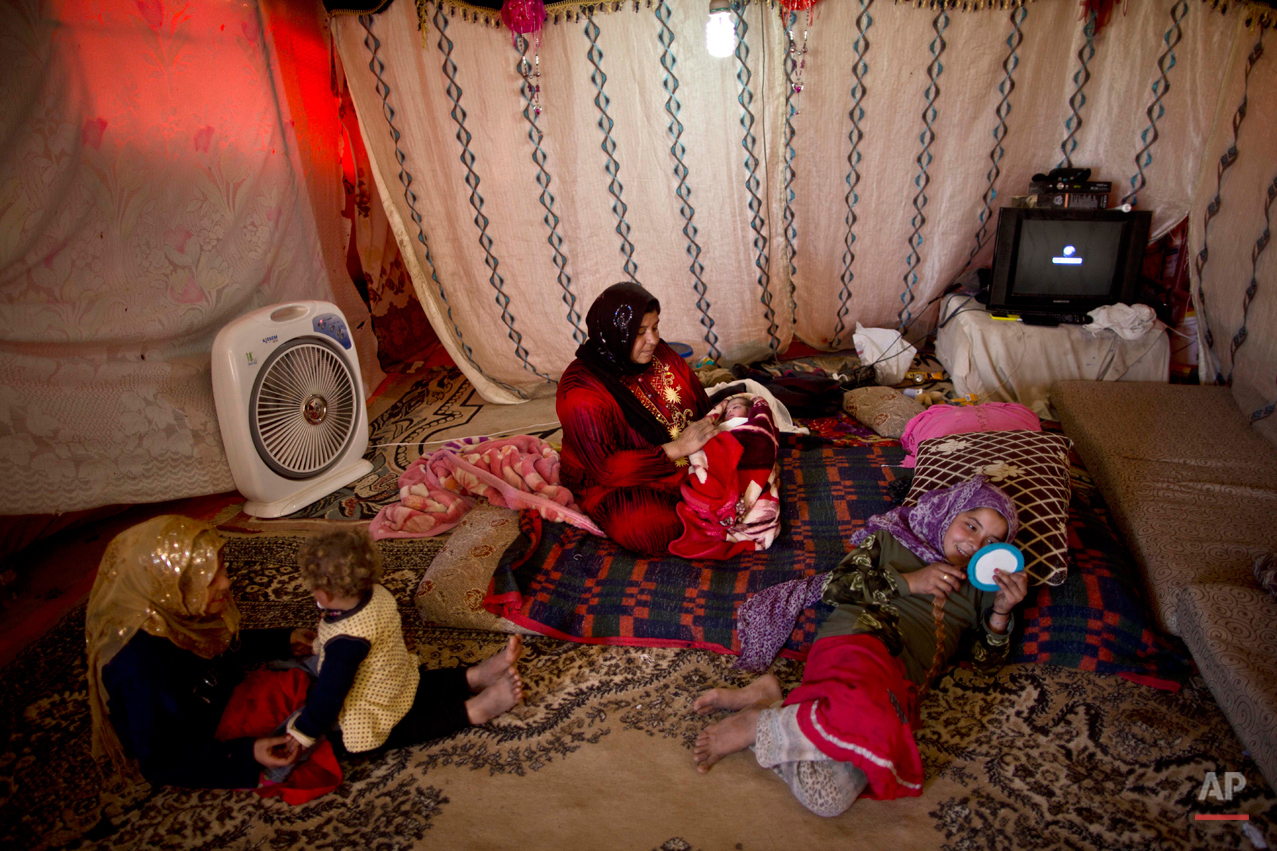 In this Friday, March 6, 2015 photo, Syrian refugee Fatima Jassim, 39, holds her newborn daughter as her other children play in their tent in an informal tented settlement in the Jordan Valley, Jordan. Jassim says she struggles to feed her newborn. ìI want to see my 3-day-old daughter Marwa grow up under a roof, safe and healthy,î she says. ìI want to give her what I could not give her elder sisters, a good childhood.î(AP Photo/Muhammed Muheisen)