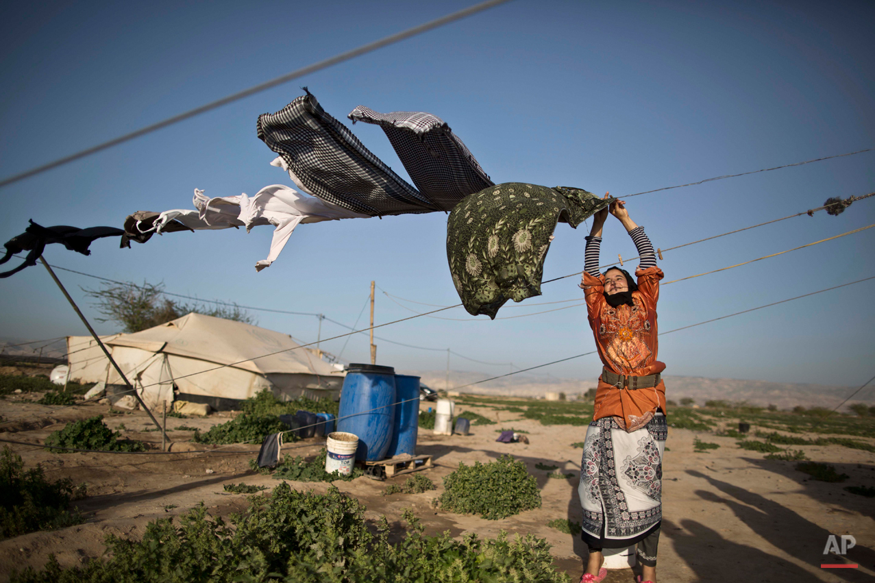 In this Friday, March 6, 2015 photo, a Syrian refugee hangs her laundry to dry at an informal tented settlement in the Jordan Valley, Jordan. Aid officials say those in the makeshift camps are among the most vulnerable of close to 625,000 Syrians who fled to Jordan and have registered with the U.N. refugee agency.(AP Photo/Muhammed Muheisen)