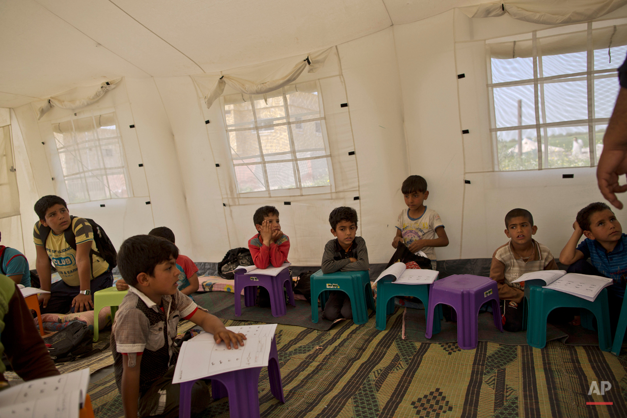 In this Monday, March 9, 2015 photo, Syrian refugee children listen to their teacher Mohammed al-Marahla, 42, a Jordanian who volunteered to teach them 6 days a week, at a makeshift school in a tent in an informal tented settlement in Al-Aghwar, Jordan, near the Israeli border. In June 2014, a survey commissioned by UNICEF said there were 125 informal tent settlements for Syrian refugees across Jordan, home to some 10,000 people. The survey said nearly 80 percent there were younger than 18. (AP Photo/Muhammed Muheisen)