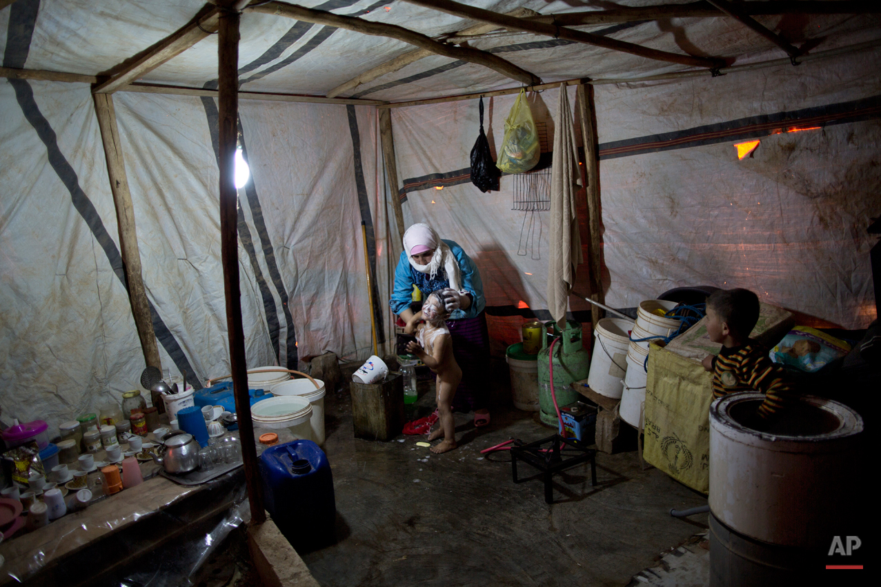 In this Sunday, March 8, 2015 photo, Syrian refugee Nisreen Sami, 23, bathes her son Mohammed, 3, at their tent in an informal tented settlement near the Syrian border, on the outskirts of Mafraq, Jordan. In Jordan, most refugees settle in urban areas. Just over 100,000 live in the three main authorized refugee camps in northern Jordan.(AP Photo/Muhammed Muheisen)