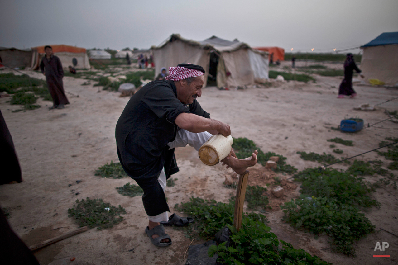 In this Friday, March 6, 2015 photo, a Syrian refugee washes his foot outside his tent at an informal tented settlement in the Jordan Valley, Jordan. In Jordan, most refugees settle in urban areas. Just over 100,000 live in the three main authorized refugee camps in northern Jordan. (AP Photo/Muhammed Muheisen)
