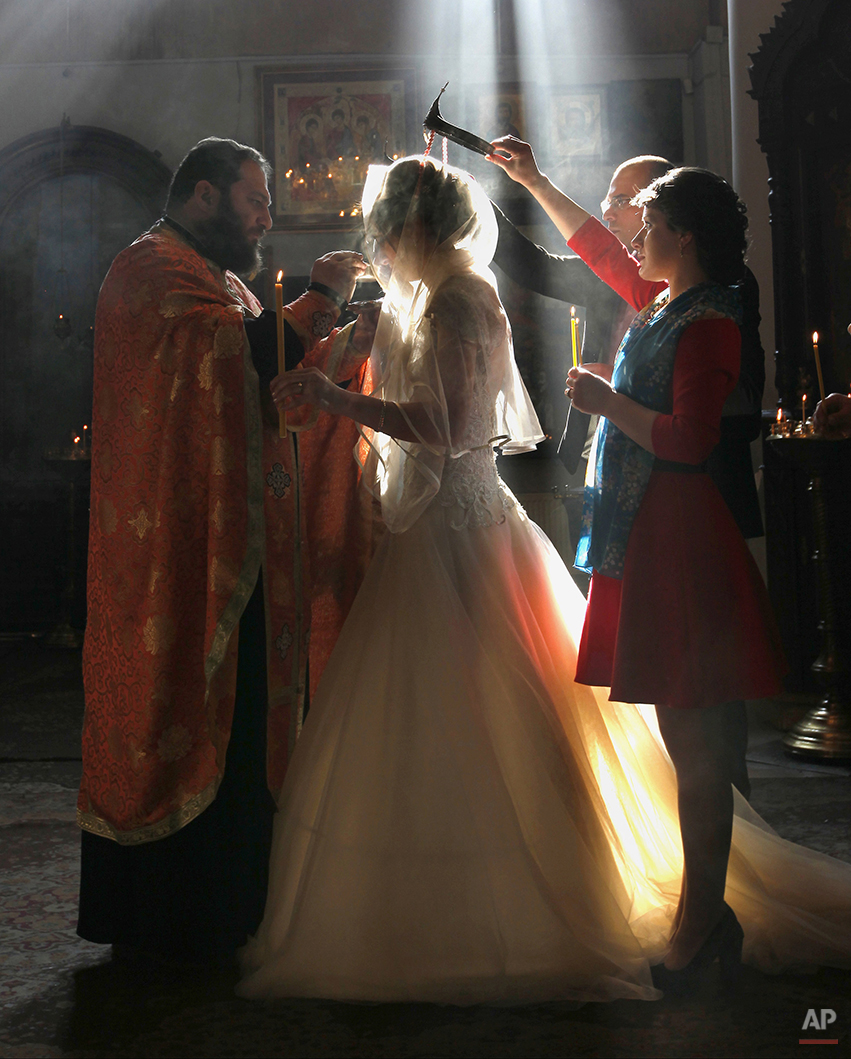 In this photo taken Saturday, Jan. 31, 2015, a Georgian Orthodox clergyman blesses newly weds during a religious ceremony at an Orthodox cathedral in Tbilisi, Georgia. (AP Photo/Shakh Aivazov)