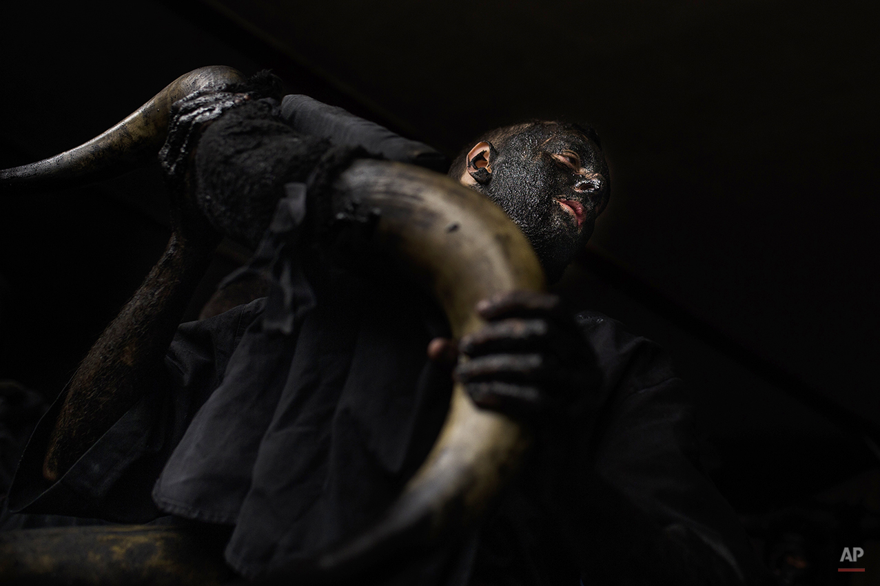 A man, covered in oil and soot carries bull horns representing the devil as he gets ready to participate during a traditional carnival celebration in the small village of Luzon, Spain, Saturday, Feb. 14, 2015. Preserved records from the 14th century document Luzon's carnival, but the real origin of the tradition could be much older. Carnival festivals are celebrated in their own way around hundreds of villages in Spain. (AP Photo/Andres Kudacki)