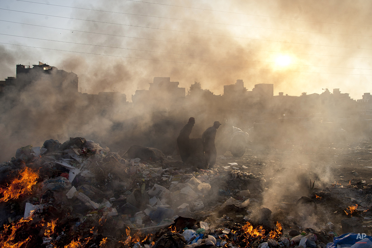Afghan refugees collect recyclable items from a a heap of garbage to earn their livings, Wednesday, Jan. 28, 2015. (AP Photo/Shakil Adil)