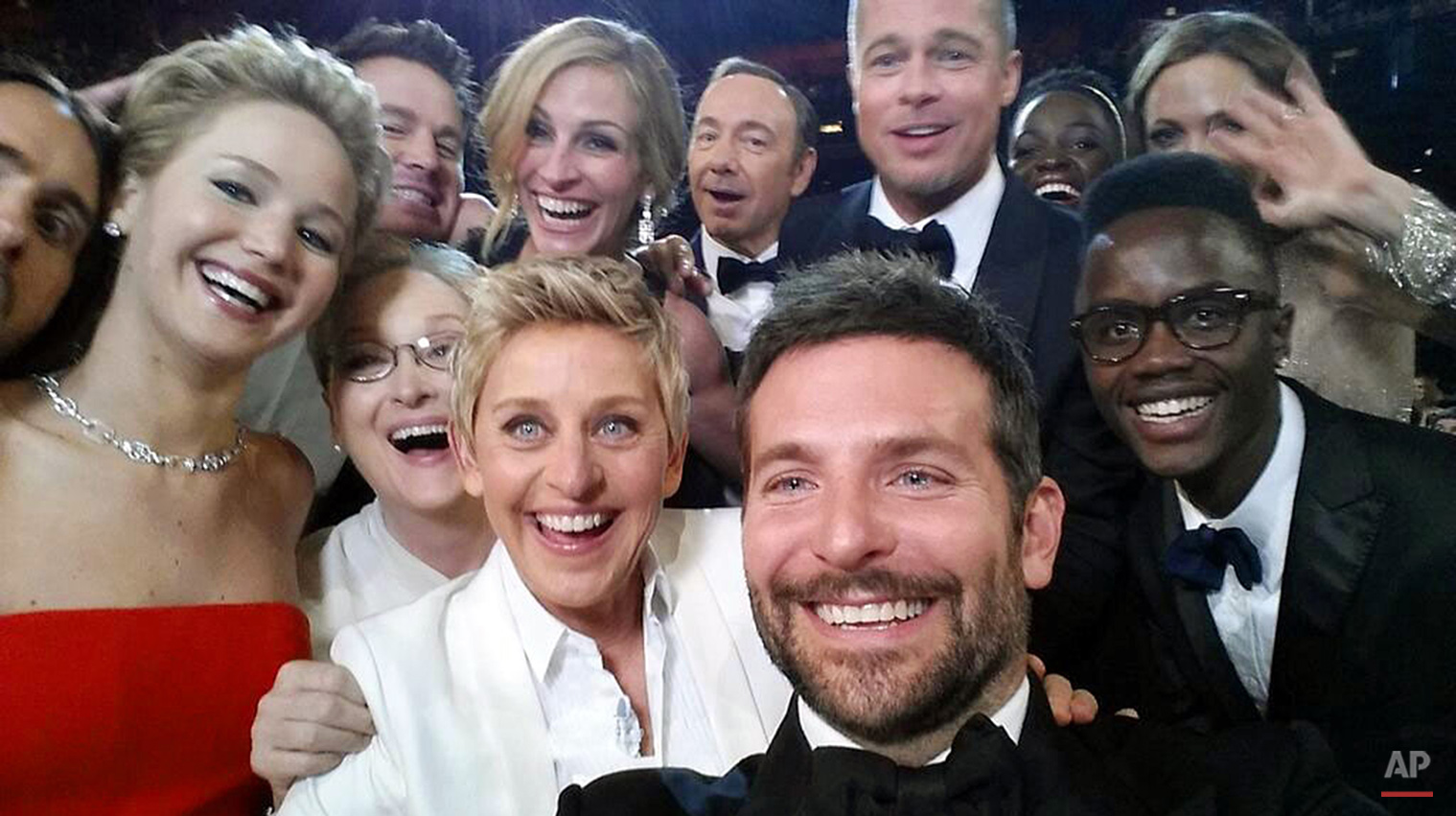 "This image released by Ellen DeGeneres shows actors, front row from left, Jared Leto, Jennifer Lawrence, Meryl Streep, Ellen DeGeneres, Bradley Cooper, Peter Nyong'o Jr. and, second row, from left, Channing Tatum, Julia Roberts, Kevin Spacey, Brad Pitt, Lupita Nyong'o and Angelina Jolie as they pose for a ""selfie"" portrait on a cell phone during the Oscars at the Dolby Theatre on Sunday, March 2, 2014, in Los Angeles. (AP Photo/Ellen DeGeneres)"