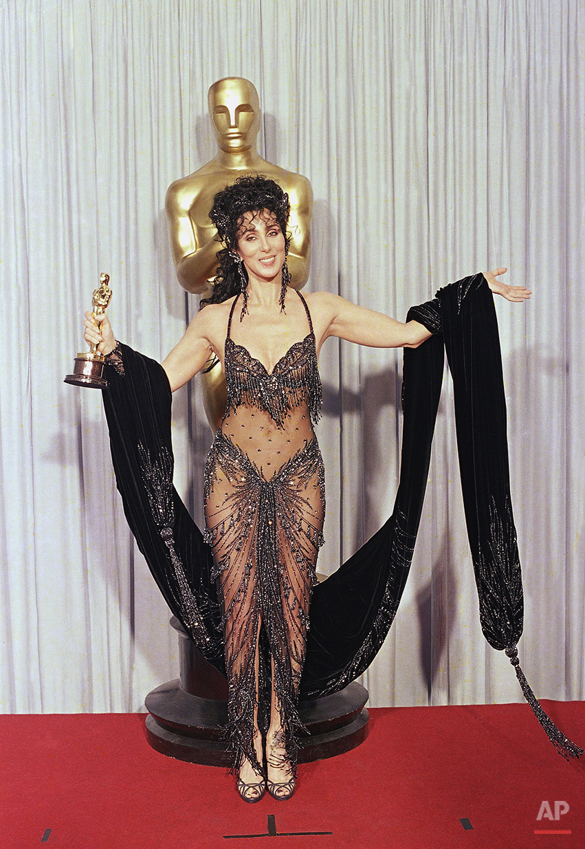 "Cher shows off both her Oscar and Bob Mackie black-sequined gown after winning the award for best actress for her role as the superstitious young widow of ""Moonstruck"" at the 60th Annual Academy Awards, April 12, 1988 in Los Angeles. (AP Photo/Lennox McLendon)"