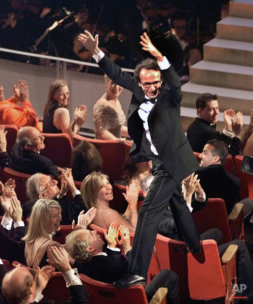"Director and actor Roberto Benigni jumps on the back of some chairs in excitement after winning the Oscar for best foreign language film for ""Life is Beautiful,"" during the 71st Annual Academy Awards at the Dorothy Chandler Pavilion of the Los Angeles Music Center, Sunday, March 21, 1999. (AP Photo/Eric Draper)"