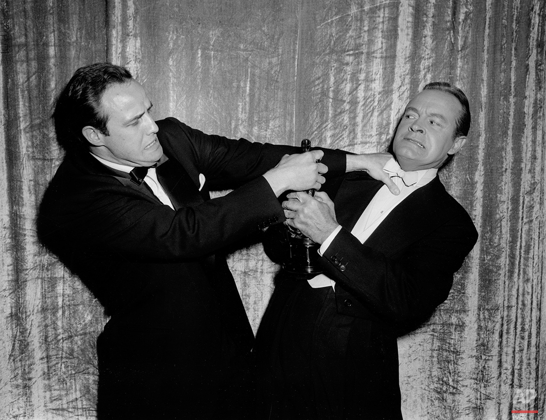 "Actor Marlon Brando defends his statuette in a mock tussle with comedian Bob Hope, during the 27th annual Academy Awards show at Pantages Theater in Hollywood, Calif., March 30, 1955.  Brando won best actor for his performance in ""On the Waterfront.""  (AP Photo)"