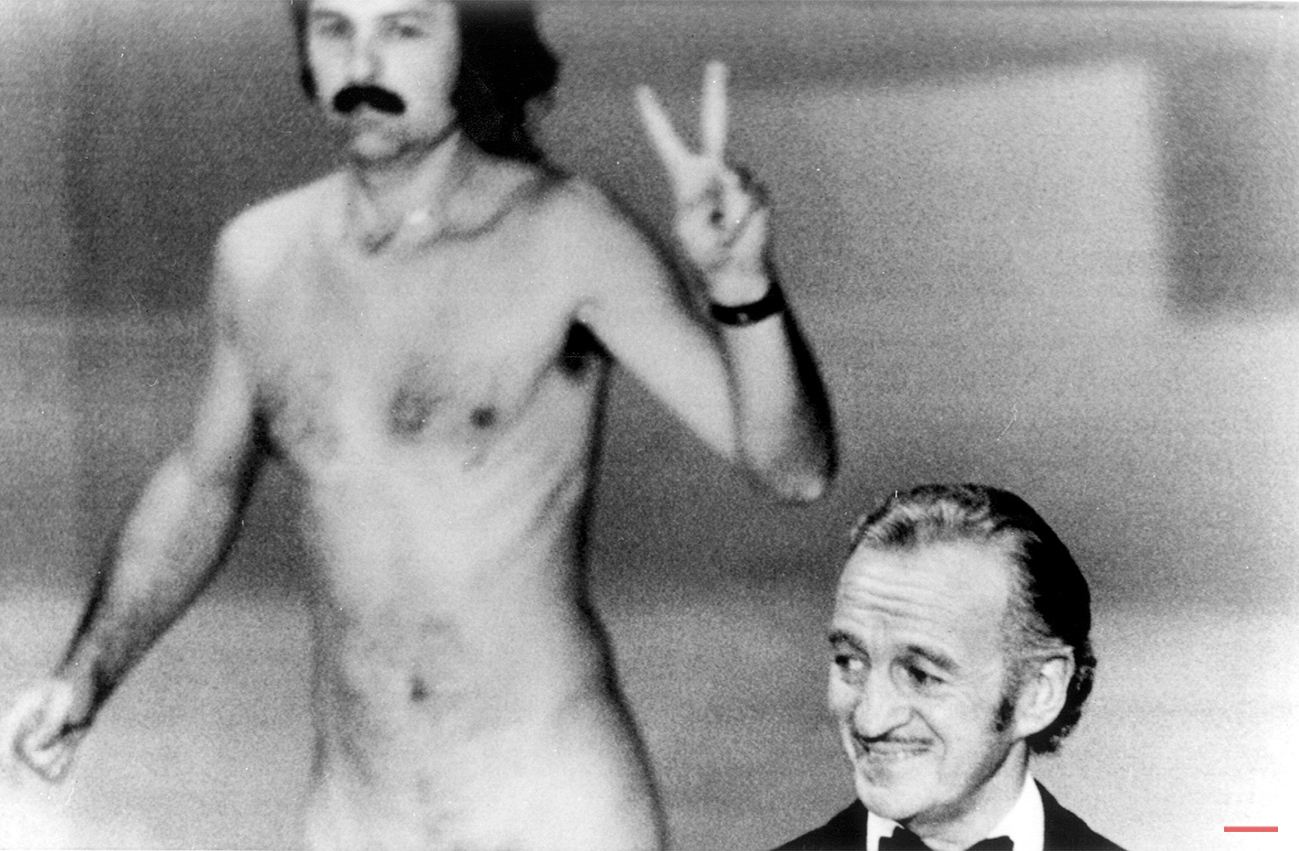 A streaker performs at academy show. David Niven isn't quite sure what's happening behind him as a streaker crosses the stage near the end of the Academy Awards show in Los Angeles tonight. He later identified himself as Robert Opel. (AP Photo)
