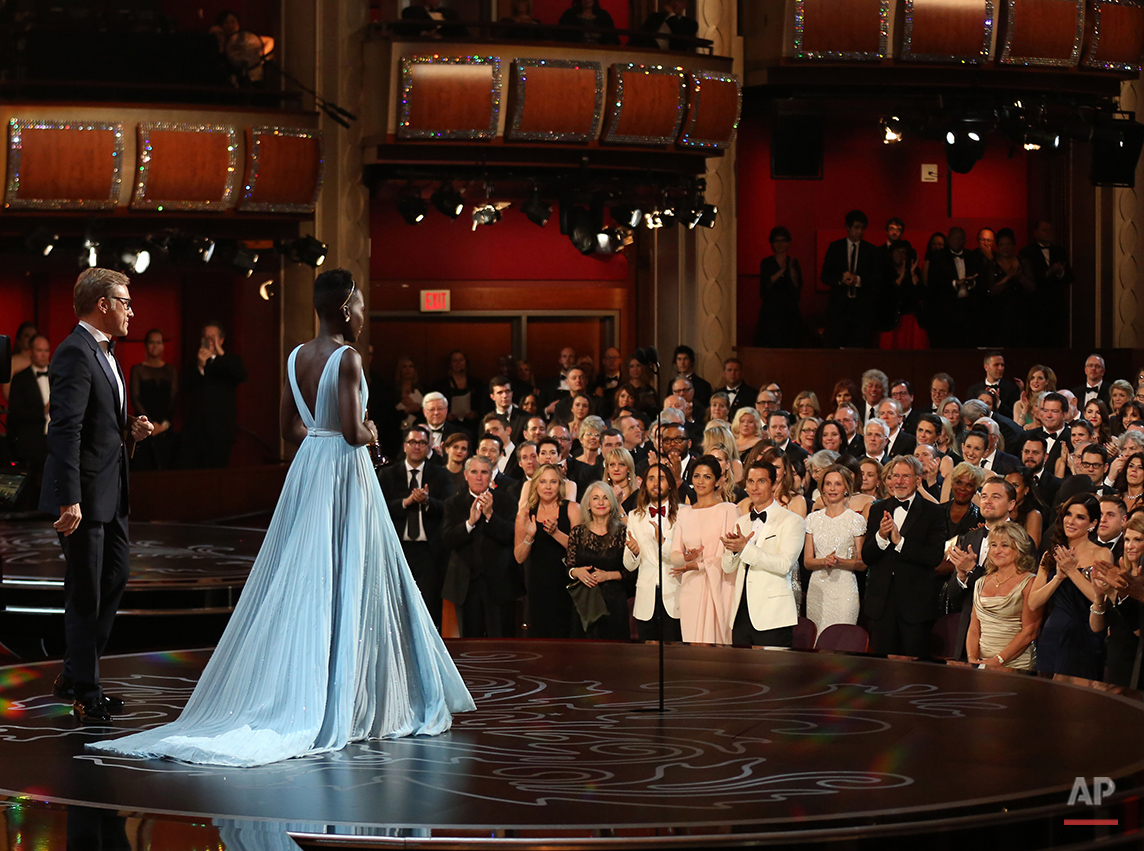 "Lupita Nyong'o receives a standing ovation as she accepts the award for best actress in a supporting role for ""12 Years a Slave"" during the Oscars at the Dolby Theatre on Sunday, March 2, 2014, in Los Angeles.  (Photo by Matt Sayles/Invision/AP)"