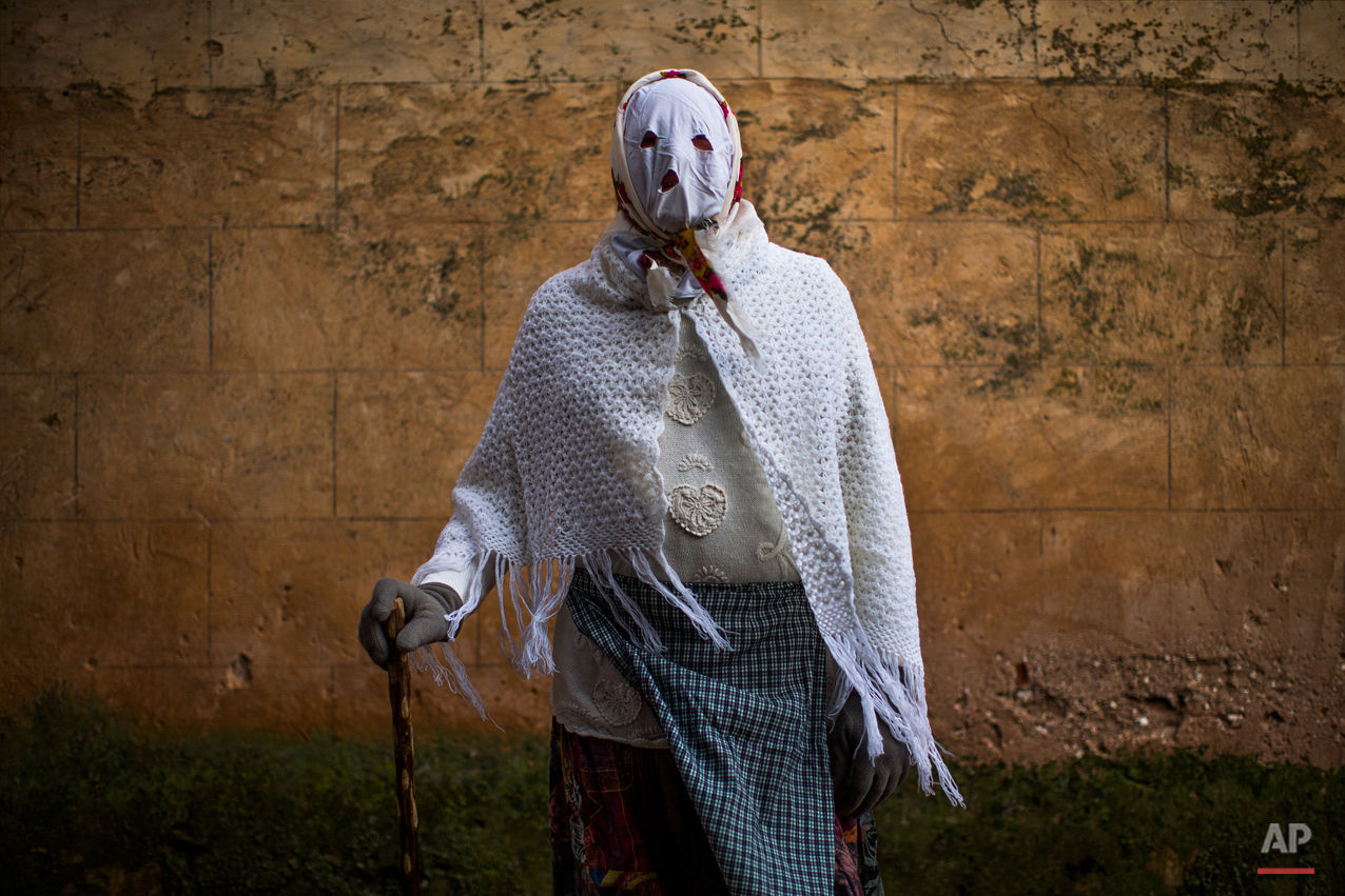 In this photo taken on Saturday, Feb. 14, 2015 a reveller wearing a costume, poses for a picture during a traditional carnival celebration in the small village of Luzon, Spain. While Rio de Janeiro may boast the worldís most famous carnival, the festive period of masquerades and wild and colorful costumes that precedes the Christian religious season of Lent is also a permanent and popular fixture for celebration in Spain and Portugal, with each country having its own strange and unique way of doing it. In Spainís central town of Luzon, men covered in oil and soot wear bull horns and cowbells to represent the devil. Records of Luzonís carnival date as far back as the 14th century although it is believed to be much older. (AP Photo/Andres Kudacki)