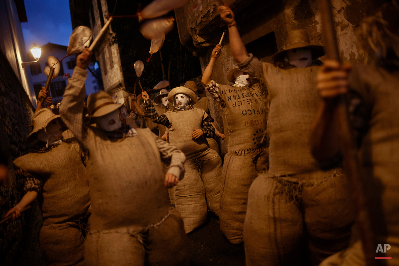 In this photo taken on Sunday, Feb. 15, 2015 revelers dressed as the traditional carnival characters 'Zaku Zaharrak', or old sack in Basque language, walk during the carnival parade of the small village of Lesaka, Spain. While Rio de Janeiro may boast the worldís most famous carnival, the festive period of masquerades and wild and colorful costumes that precedes the Christian religious season of Lent is also a permanent and popular fixture for celebration in Spain and Portugal, with each country having its own strange and unique way of doing it. In the northern Basque village of Lesaka, the central character is the 'Zaku Zaharrak,' which sees revelers stuffing themselves into sacks full of straw and threatening people with sticks bearing inflated animal bladders. (AP Photo/Daniel Ochoa de Olza)