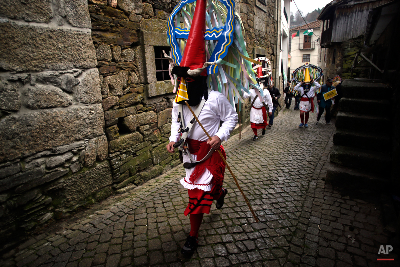 In this photo taken on Saturday, Feb. 14, 2015 revellers  dressed in Carnival traditional costumes dance and jump as they parade during Carnival festivities in Lazarim, northeastern Portugal. While Rio de Janeiro may boast the worldís most famous carnival, the festive period of masquerades and wild and colorful costumes that precedes the Christian religious season of Lent is also a permanent and popular fixture for celebration in Spain and Portugal, with each country having its own strange and unique way of doing it. Portugalís most famous carnival takes place in the north-central town of Lazarin, with its pagan ëcaretoí ritual of masked young men dressed in colored woolen quilts and donning brass, leather or wooden masks as they dance and chase local people _ especially young women _ through the streets, trying to scare them by making lots of noise and jingling bells on their backs. (AP Photo/Francisco Seco)