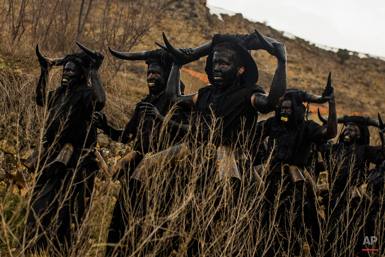 In this photo taken on Saturday, Feb. 14, 2015 men covered in oil and soot carrying bull horns on their head and cowbells on a belt representing devils, march during a traditional carnival celebration in the small village of Luzon, Spain. While Rio de Janeiro may boast the worldís most famous carnival, the festive period of masquerades and wild and colorful costumes that precedes the Christian religious season of Lent is also a permanent and popular fixture for celebration in Spain and Portugal, with each country having its own strange and unique way of doing it. In Spainís central town of Luzon, men covered in oil and soot wear bull horns and cowbells to represent the devil. Records of Luzonís carnival date as far back as the 14th century although it is believed to be much older. (AP Photo/Andres Kudacki)