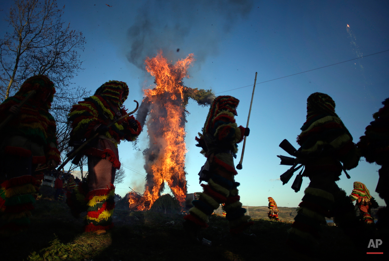 In this photo taken on Tuesday, Feb. 17, 2015 revellers dressed in traditional costumes run around a burning effigy of a traditional figure during annual Carnival festivities, in Podence, northeastern Portugal. While Rio de Janeiro may boast the worldís most famous carnival, the festive period of masquerades and wild and colorful costumes that precedes the Christian religious season of Lent is also a permanent and popular fixture for celebration in Spain and Portugal, with each country having its own strange and unique way of doing it. Portugalís most famous carnival takes place in the north-central town of Lazarin, with its pagan ëcaretoí ritual of masked young men dressed in colored woolen quilts and donning brass, leather or wooden masks as they dance and chase local people _ especially young women _ through the streets, trying to scare them by making lots of noise and jingling bells on their backs. (AP Photo/Francisco Seco)