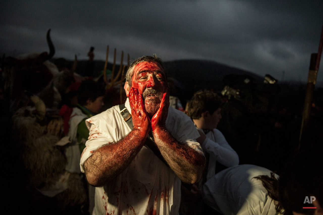 In this photo taken on Tuesday, Feb. 17, 2015 a man covers his face with blood to takes part in the ''Momotxorro Carnival'',  in Alsasua, northern Spain. While Rio de Janeiro may boast the worldís most famous carnival, the festive period of masquerades and wild and colorful costumes that precedes the Christian religious season of Lent is also a permanent and popular fixture for celebration in Spain and Portugal, with each country having its own strange and unique way of doing it. Up north in Alsasua, Spain,  half-man, half-bull figures known as Momotxorros smear their face as if with the blood of a sacrificed animal. Wearing horns and and red-stained, white sheets, they roam the town roaring fiercely and brandishing sticks.  (AP Photo/Alvaro Barrientos)