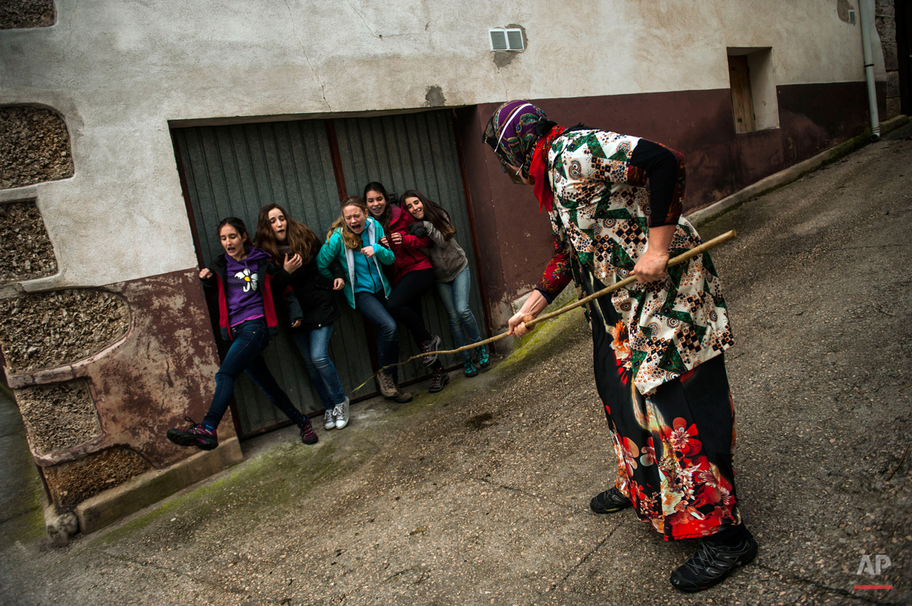 In this photo taken on Sunday, Feb. 15, 2015 a group of  young girls react next to a ''Mamuxarro'' during the carnival, in the small town of Unanu, northern Spain,  While Rio de Janeiro may boast the worldís most famous carnival, the festive period of masquerades and wild and colorful costumes that precedes the Christian religious season of Lent is also a permanent and popular fixture for celebration in Spain and Portugal, with each country having its own strange and unique way of doing it. In the northern Spanish ancient village of Unamu, people dress up as 'Mamuxarroí, folkloric figures in white with a red sash and a metal mask to cover their faces as they pursue townsfolk with sticks. According to custom, their 'victims' (usually young women) must kneel and kiss the mamuxarroís knee after he makes the sign of the cross on their forehead. (AP Photo/Alvaro Barrientos)