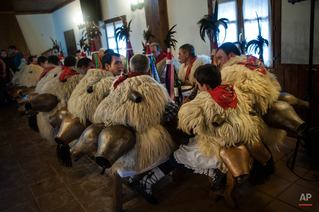 In this photo taken on Tuesday, Jan. 27, 2015 Joaldunaks, also called ''Zanpantzar'', eat in a restaurant on their way to take part on the Carnival between of the Pyrenees villages of Ituren and Zubieta, northern Spain.  While Rio de Janeiro may boast the worldís most famous carnival, the festive period of masquerades and wild and colorful costumes that precedes the Christian religious season of Lent is also a permanent and popular fixture for celebration in Spain and Portugal, with each country having its own strange and unique way of doing it. The Pyrenees villages of Ituren and Zubieta stage one of Europeís most ancient carnivals _ dating from Roman times _ where residents dress up as figures known as ëJoaldunak,í _ or cowbells _ and parade the streets with sheepskins around the waist and shoulder, conical caps and cowbells on their back. (AP Photo/Alvaro Barrientos)