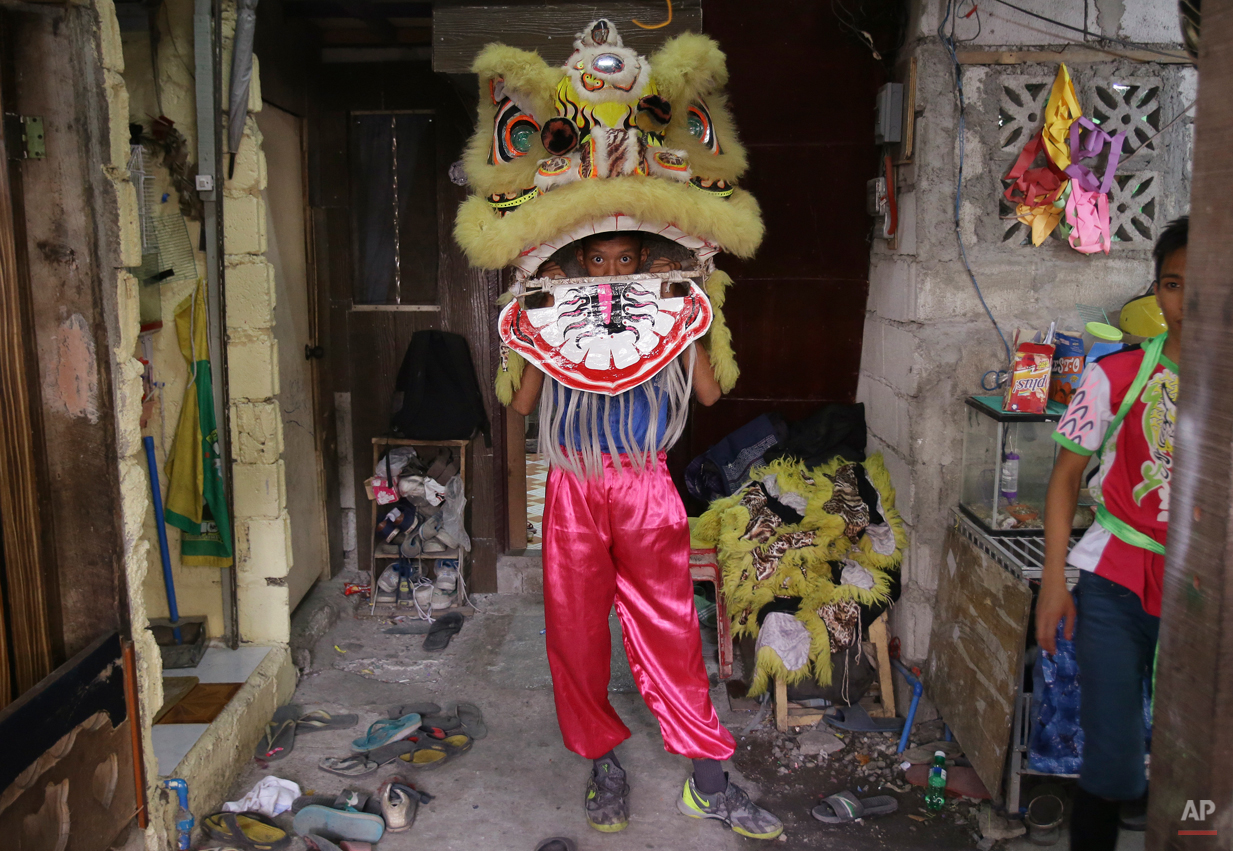 In this Wednesday, Feb. 18, 2015 photo, a Filipino lion dancer checks his costume as he prepares for a performance in Manila's Chinatown, Philippines. The Pink Panther Dragon and Lion Dance Group, a business operated by eight Filipino siblings who live in a creekside slum in Manilaís Chinatown area, are hired by businesses that believe a Chinese New Year peformance will drive misfortunes away and bring good luck. (AP Photo/Aaron Favila)