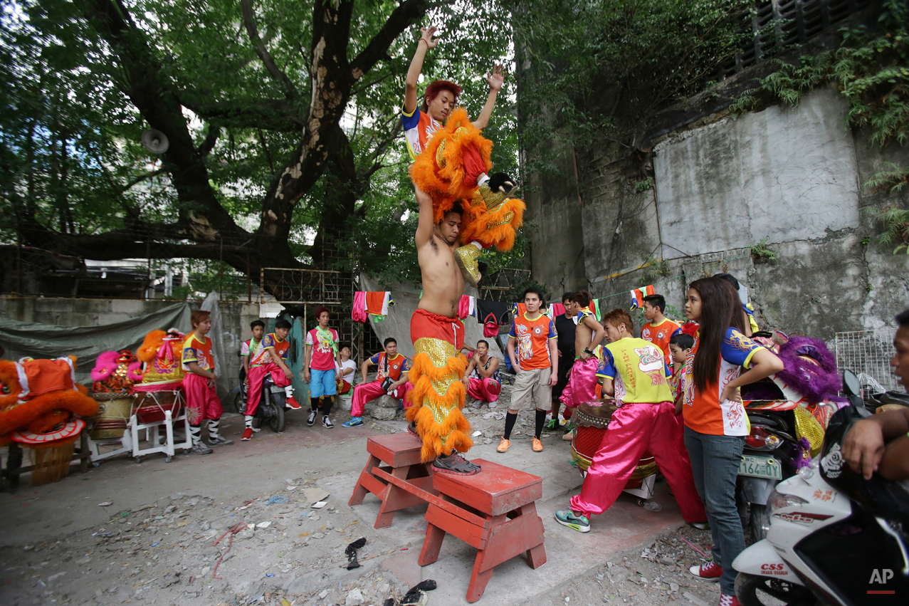 In this Wednesday, Feb. 18, 2015 photo, Filipino lion dancer Jhayvee Sicat, top and his cousin practice at their compound in the Chinatown area of Manila, Philippines. The dance company started 10 years ago with only two Chinese lion heads. Now they have 25 lion heads, nine dragons and a team of 100 workers. (AP Photo/Aaron Favila)