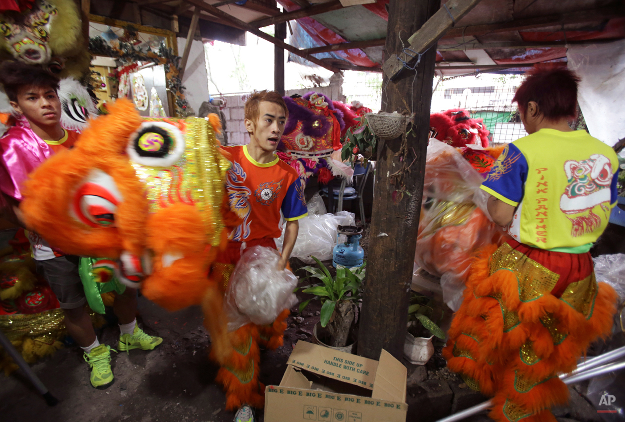 """In this Wednesday, Feb. 18, 2015 photo, performer Therry Sicat carries the head of a Chinese lion as the Pink Panther Dragon and Lion Dance Group, prepares for their next performance at the Chinatown area of Manila, Philippines. """"We got the name Pink Panther because when we started we were the first ones who had a pink lion,î Manager Joseph Sicat said. ìWe added ëPantherí because we think it sounds fierce.î (AP Photo/Aaron Favila)"""