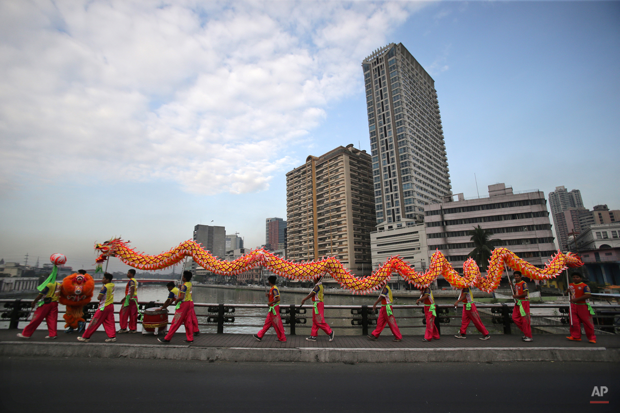 In this Wednesday, Feb. 18, 2015, photo, Filipino lion and dragon dancers walk to their next performance in Manila, Philippines. The dance group's manager, Joseph Sicat, says itís hard work to transport the performers, costumes and equipment from show to show. (AP Photo/Aaron Favila)