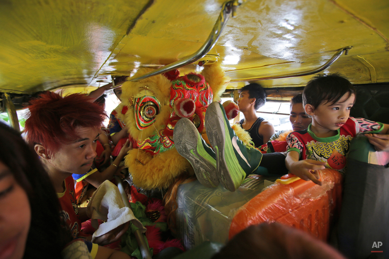 In this Wednesday, Feb. 18, 2015, photo, Filipino lion and dragon dancers cram inside their vehicle headed to their next performance in Manila, Philippines. The dance group is hired by businesses that believe the show will drive misfortunes away and bring good luck. (AP Photo/Aaron Favila)