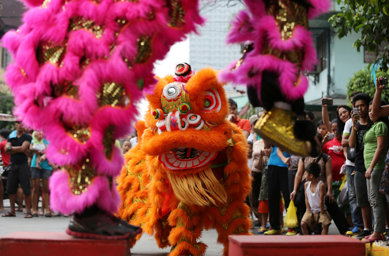 In this Wednesday, Feb. 18, 2015, photo, a crowd gathers to watch as Filipino lion dancers perform in Manila, Philippines. The Chinese New Year performance is by the Pink Panther Dragon and Lion Dance Group, a business operated by eight Filipino siblings who live in a creekside slum in Manilaís Chinatown area. (AP Photo/Aaron Favila)