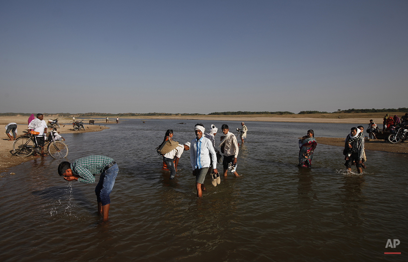 In this photo taken Monday, April 28, 2014, an Indian drinks straight from the river as villagers wade through the shallow waters after crossing the River Chambal in a ferry near Bhopepura village in the northern Indian state of Uttar Pradesh. A narrow 250-mile stretch of the Chambal was declared an official sanctuary in the late 1970s, closing it to everyone but longtime villagers, approved scientists and the handful of tourists who make it here. But with India's economic growth came troubles that threaten the Chambal and its wildlife: polluting factories, illegal sand mining and fish poachers who hack at gharials with axes when the animals get tangled in their nets. (AP Photo/Altaf Qadri)