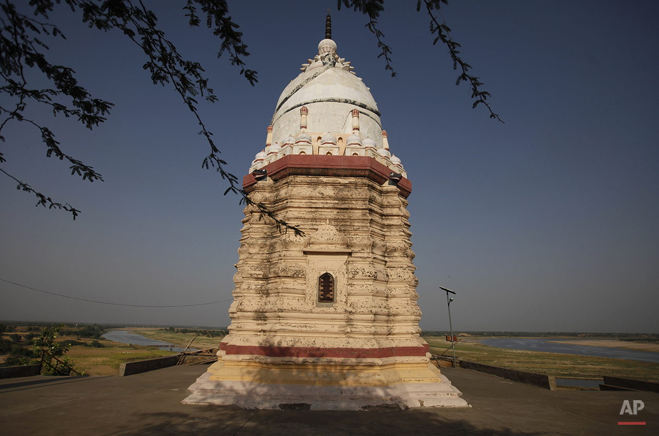 In this photo taken Tuesday, April 29, 2014, an old temple stands near the confluence of the Rivers Yamuna, seen on left, and Chambal, on right, in Bhareh village in the northern Indian state of Uttar Pradesh. The fears that shaped this region go back more than a thousand years, to when sages said the Chambal (the term refers both to the river and the rugged land around it) had been cursed and villagers whispered that it was unholy. In a culture where rivers have long been worshipped, farmers avoided planting along the river's banks. (AP Photo/Altaf Qadri)