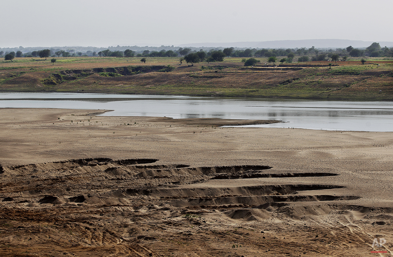 In this photo taken Wednesday, April 30, 2014, pits are seen on the Chambal riverbank, dug out by illegal sand miners near Sagarpada, in the western Indian state of Rajasthan. A narrow 250-mile stretch of the Chambal was declared an official sanctuary in the late 1970s, closing it to everyone but longtime villagers, approved scientists and the handful of tourists who make it here. But the most immediate worry to the sanctuary is illegal sand mining, which can strip away thousands of tons of riverbank on a single day, causing immense amounts of silt to spill into the river, upsetting its delicate ecology. (AP Photo/Altaf Qadri)