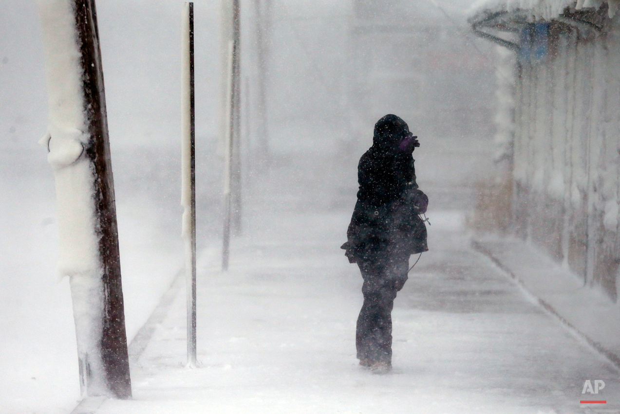 A woman braces against the wind during a winter storm in Marshfield, Mass., Tuesday, Jan. 27, 2015. The storm punched out a section of the seawall in the coastal town of Marshfield, police said.(AP Photo/Michael Dwyer)