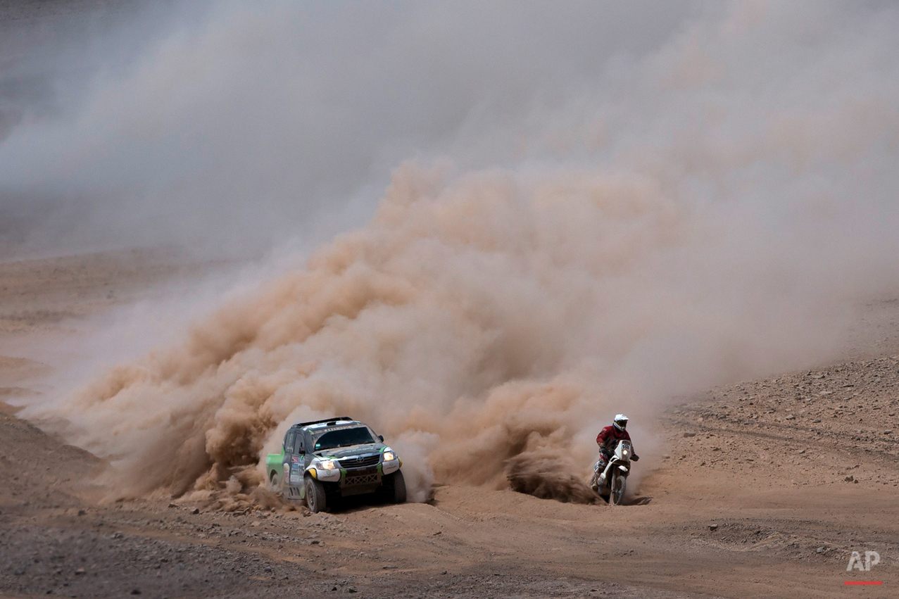 Toyota driver Yazeed Alrajhi, from Saudi Arabia, and co-pilot Timo Gottschalk, from Germany, left, overtake KTM motorcyclist Damien Udry, from Switzerland, during the ninth stage of the Dakar Rally between the cities of Iquique and Calama, Chile, Tuesday, Jan. 13, 2015. The race will finish on Jan. 17, passing through Bolivia and Chile before returning to Argentina where it started. (AP Photo/Felipe Dana)