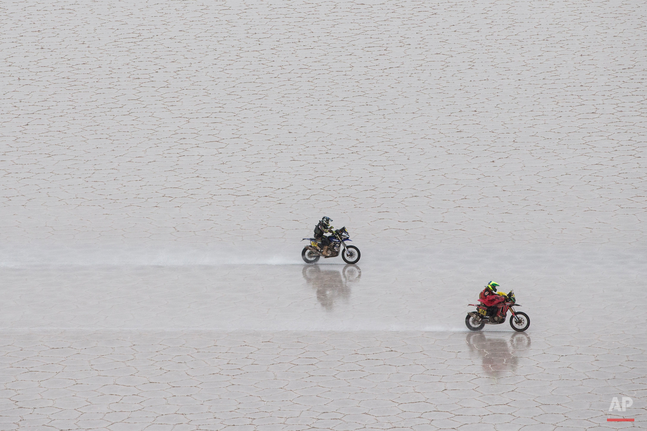 Honda rider Jean de Azevedo of Brazil, right, leads Yamaha rider Michael Metge of France, as they race across the Uyuni salt flat during the eighth stage of the Dakar Rally 2015 between Uyuni, Bolivia, and Iquique, Chile, Monday, Jan. 12, 2015. Chileís Pablo Quintanilla won the motorcycle eighth stage of the Rally, while Spainís Marc Coma took the overall lead. (AP Photo/Felipe Dana)