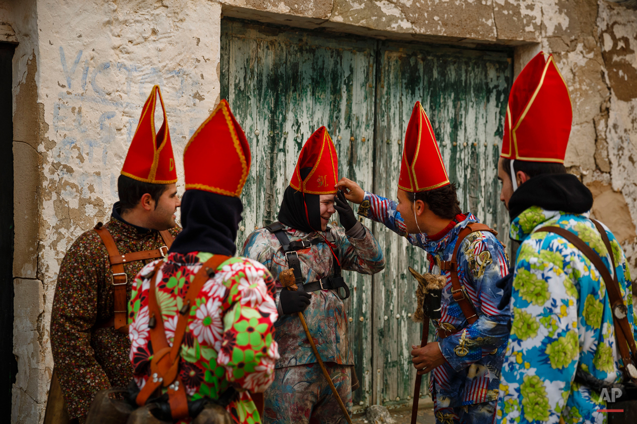 "Members of the Endiablada brotherhood joke during the 'Endiablada' traditional festival in Almonacid Del Marquesado, Spain, Tuesday, Feb. 3, 2015. The ""Endiablada"" (The Brotherhood of the Devils) festivals are celebrated each Feb. 2-3 in the central Spanish town of Almonacid del Marquesado since medieval times or before. In the festival, men from the town dress up as devil-type characters in colorful jumpsuit costumes and red miter hats. They don large heavy copper cowbells around their waists, which clang incessantly as they walk, dance and jump through the town's winding streets and visit the cemetery. The Feb. 3 day procession commemorates the day of Saint Blas. According to a local legend, town shepherds found a statue of the saint and then won a competition with folk from a nearby town to keep the effigy and rang the bells of their animals in celebration. (AP Photo/Daniel Ochoa de Olza)"