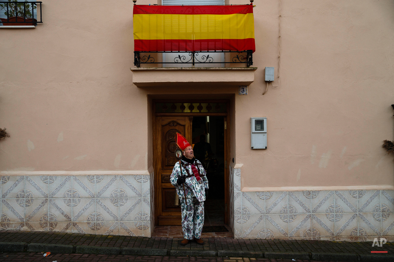 "Aniceto Rodrigo, 78, Diablo Mayor or 'greater devil', checks the weather as he leaves his home before walking around the village during the 'Endiablada' traditional festival in Almonacid Del Marquesado, Spain, Tuesday, Feb. 3, 2015. The ""Endiablada"" (The Brotherhood of the Devils) festivals are celebrated each Feb. 2-3 in the central Spanish town of Almonacid del Marquesado since medieval times or before. In the festival, men from the town dress up as devil-type characters in colorful jumpsuit costumes and red miter hats. They don large heavy copper cowbells around their waists, which clang incessantly as they walk, dance and jump through the town's winding streets and visit the cemetery. The Feb. 3 day procession commemorates the day of Saint Blas. According to a local legend, town shepherds found a statue of the saint and then won a competition with folk from a nearby town to keep the effigy and rang the bells of their animals in celebration. (AP Photo/Daniel Ochoa de Olza)"