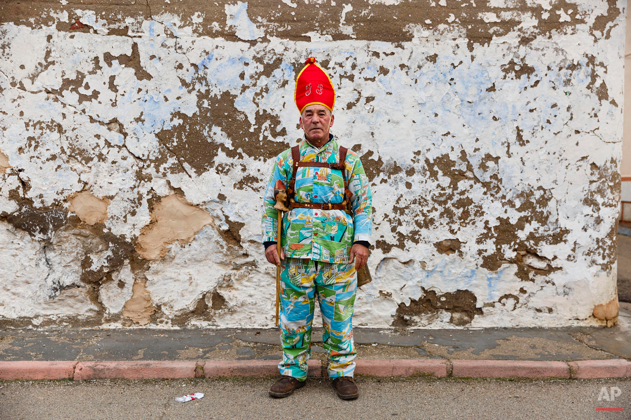 "A member of the Endiablada brotherhood poses for a picture during the 'Endiablada' traditional festival in Almonacid Del Marquesado, Spain, Tuesday, Feb. 3, 2015. During the Endiablada, or 'The Brotherhood of the Devils' believers dressed in colorful costumes, wearing a red mitre and big copper cowbells hanging tied to their waists make lot of noise as they walk, dance or jump around streets if the tiny village, and during its procession, in front of the a sculpture depicting the Virgin or the Saint. In the ""Endiablada"", is a tradition that has survived through the centuries in honor of the Candelaria's Virgin and San Blas. Candelaria, refers to the Jewish protocol, in which the Virgin Mary had to present her new baby, Jesus, to the temple, forty days after his birth. In the Catholic teachings, it is said that this action caused the Virgin Mary great anxiety and shame because of the public knowledge of the unusual circumstances of Jesusís birth. La Endiablada brotherhood with their noisy bells are said to be trying to divert the publicís attention so that the Virgin Mary could fulfill her obligation and avoid suffering such embarrassment and shame. The connection of the dancing 'diablos' to San Blas has another explanation, according to a local legend shepherds found an image of San Blas, a miraculous event took place and they understood to be a sign that the saint was meant to stay in Almonacid. As a sign of their joy the shepherds rang the bells of their cattle so giving La Endiablada their famous cowbells. (AP Photo/Daniel Ochoa de Olza)"