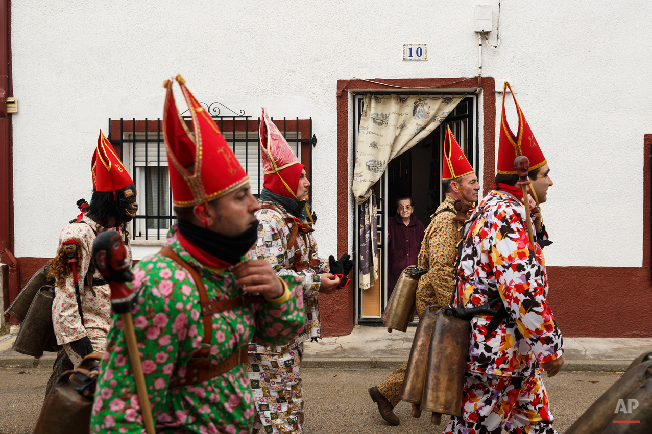 "A woman looks from her home as members of the Endiablada brotherhood march past during the 'Endiablada' traditional festival in Almonacid Del Marquesado, Spain, Tuesday, Feb. 3, 2015. The ""Endiablada"" (The Brotherhood of the Devils) festivals are celebrated each Feb. 2-3 in the central Spanish town of Almonacid del Marquesado since medieval times or before. In the festival, men from the town dress up as devil-type characters in colorful jumpsuit costumes and red miter hats. They don large heavy copper cowbells around their waists, which clang incessantly as they walk, dance and jump through the town's winding streets and visit the cemetery. The Feb. 3 day procession commemorates the day of Saint Blas. According to a local legend, town shepherds found a statue of the saint and then won a competition with folk from a nearby town to keep the effigy and rang the bells of their animals in celebration. (AP Photo/Daniel Ochoa de Olza)"