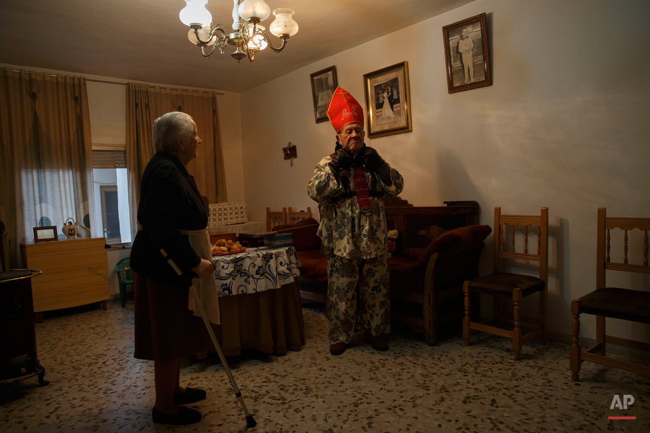 "Aniceto Rodrigo, 78, Diablo Mayor or 'greater devil', adjusts his mitre inside his home before walking around the village during the 'Endiablada' traditional festival in Almonacid Del Marquesado, Spain, Tuesday, Feb. 3, 2015. The ""Endiablada"" (The Brotherhood of the Devils) festivals are celebrated each Feb. 2-3 in the central Spanish town of Almonacid del Marquesado since medieval times or before. In the festival, men from the town dress up as devil-type characters in colorful jumpsuit costumes and red miter hats. They don large heavy copper cowbells around their waists, which clang incessantly as they walk, dance and jump through the town's winding streets and visit the cemetery. The Feb. 3 day procession commemorates the day of Saint Blas. According to a local legend, town shepherds found a statue of the saint and then won a competition with folk from a nearby town to keep the effigy and rang the bells of their animals in celebration. (AP Photo/Daniel Ochoa de Olza)"