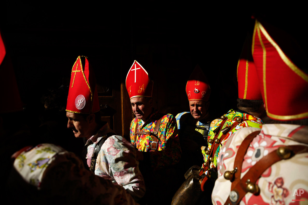 "Members of the Endiablada brotherhood leave the church during the 'Endiablada' traditional festival in Almonacid Del Marquesado, Spain, Tuesday, Feb. 3, 2015. The ""Endiablada"" (The Brotherhood of the Devils) festivals are celebrated each Feb. 2-3 in the central Spanish town of Almonacid del Marquesado since medieval times or before. In the festival, men from the town dress up as devil-type characters in colorful jumpsuit costumes and red miter hats. They don large heavy copper cowbells around their waists, which clang incessantly as they walk, dance and jump through the town's winding streets and visit the cemetery. The Feb. 3 day procession commemorates the day of Saint Blas. According to a local legend, town shepherds found a statue of the saint and then won a competition with folk from a nearby town to keep the effigy and rang the bells of their animals in celebration. (AP Photo/Daniel Ochoa de Olza)"