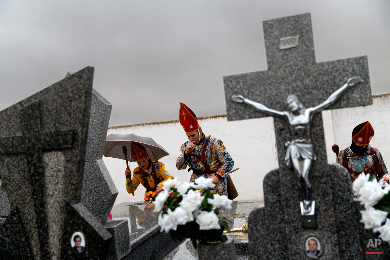 "In this Feb. 2, 2015 picture, members of the Endiablada brotherhood pray for the deceased fellow believers and relatives during the 'Endiablada' traditional festival in Almonacid Del Marquesado, Spain. The ""Endiablada"" (The Brotherhood of the Devils) festivals are celebrated each Feb. 2-3 in the central Spanish town of Almonacid del Marquesado since medieval times or before. In the festival, men from the town dress up as devil-type characters in colorful jumpsuit costumes and red miter hats. They don large heavy copper cowbells around their waists, which clang incessantly as they walk, dance and jump through the town's winding streets and visit the cemetery. The Feb. 2 procession, the ""Candelaria"" (Candlemas), represents the Virgin Mary presenting baby Jesus to authorities in the temple 40 days after Christmas. The protocol is believed to have caused her some embarrassment and the accompanying bell-clanging characters are thought to be a way of diverting the publicís attention. (AP Photo/Daniel Ochoa de Olza)"