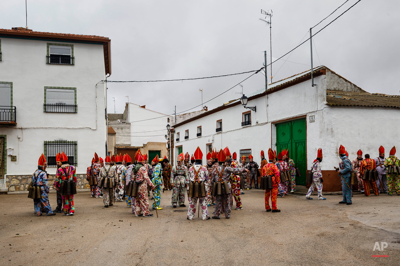 "Members of the Endiablada brotherhood gather during the 'Endiablada' traditional festival in Almonacid Del Marquesado, Spain, Tuesday, Feb. 3, 2015. The ""Endiablada"" (The Brotherhood of the Devils) festivals are celebrated each Feb. 2-3 in the central Spanish town of Almonacid del Marquesado since medieval times or before. In the festival, men from the town dress up as devil-type characters in colorful jumpsuit costumes and red miter hats. They don large heavy copper cowbells around their waists, which clang incessantly as they walk, dance and jump through the town's winding streets and visit the cemetery. The Feb. 3 day procession commemorates the day of Saint Blas. According to a local legend, town shepherds found a statue of the saint and then won a competition with folk from a nearby town to keep the effigy and rang the bells of their animals in celebration. (AP Photo/Daniel Ochoa de Olza)"