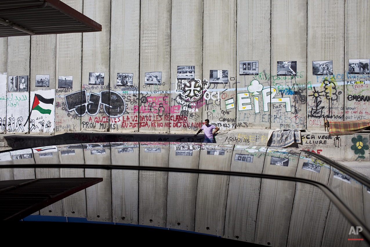 A Palestinian walks past a section of Israel's separation barrier running between the biblical Tomb of Rachel, not seen, and the West Bank city of Bethlehem, Tuesday, Feb. 23, 2010. (AP Photo/Bernat Armangue)